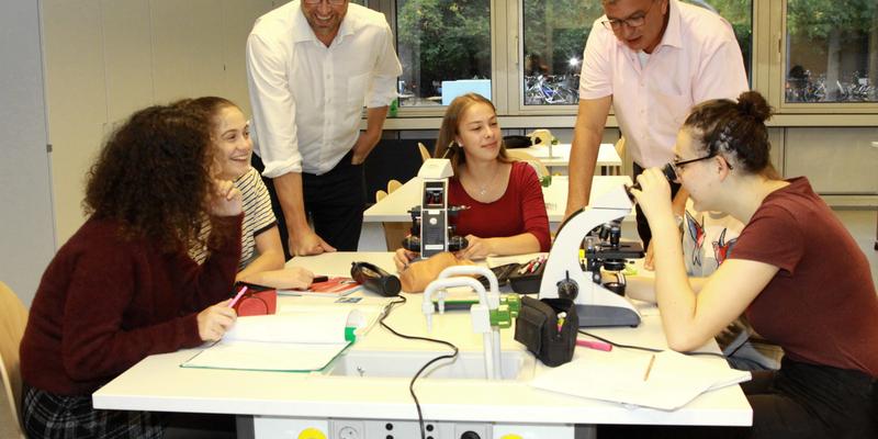 Schulleiter Dirk Stueber (links) und BM Stephan Vehreschild schauen Schülerinnen beim Mikroskopieren über die Schulter