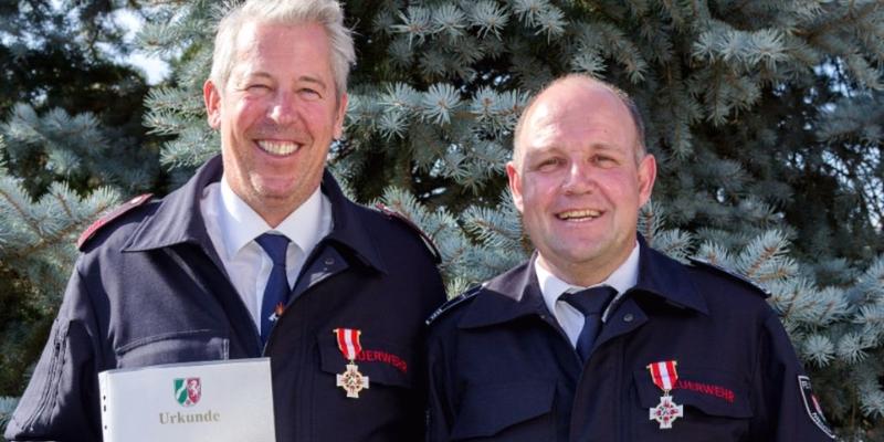 Dirk Schmitz (links) und Udo Karp mit Urkunden und Abzeichen