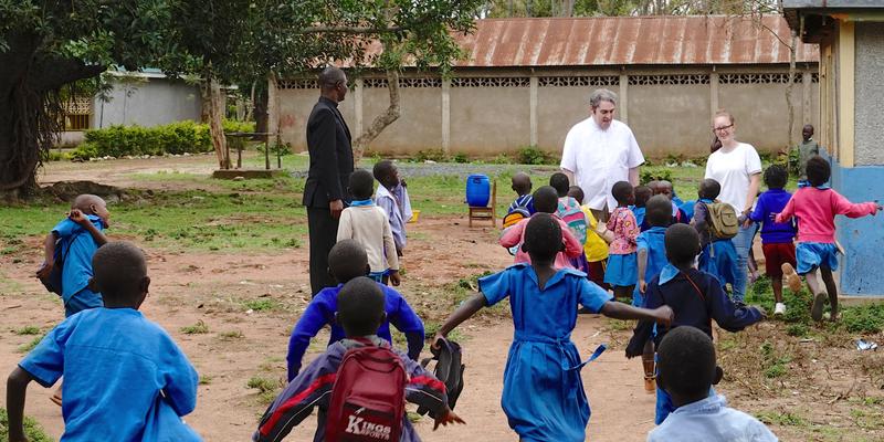 Kindergartenkinder freuen sich über den Besuch der Gäste.  In der Mitte der Rheidter Pfarrer René Stockhausen